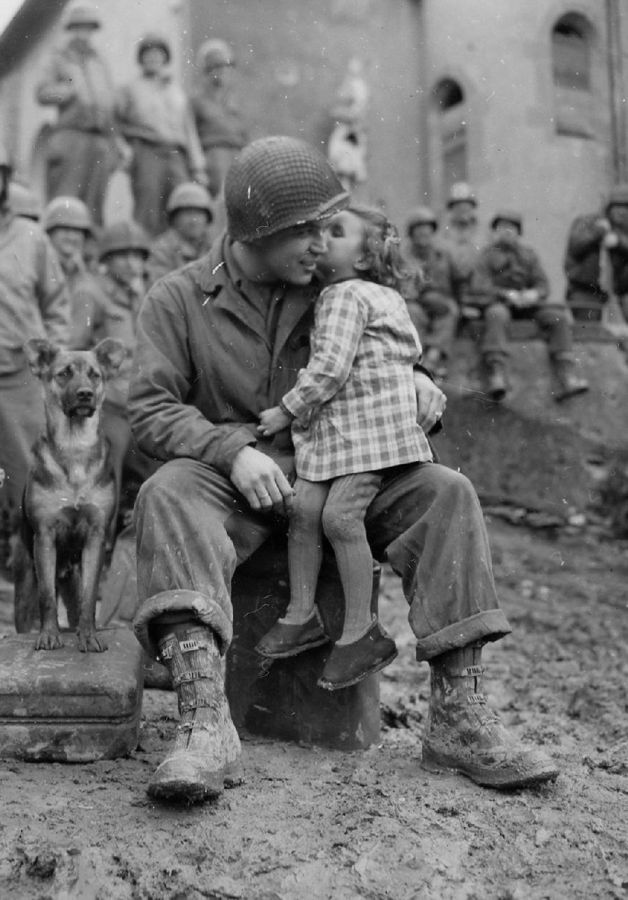 Private Alvin Harley of the 9th Armored Division gets a kiss from a little French girl with a German Shepherd by his side in Abancourt, France on Valentine's Day 1945