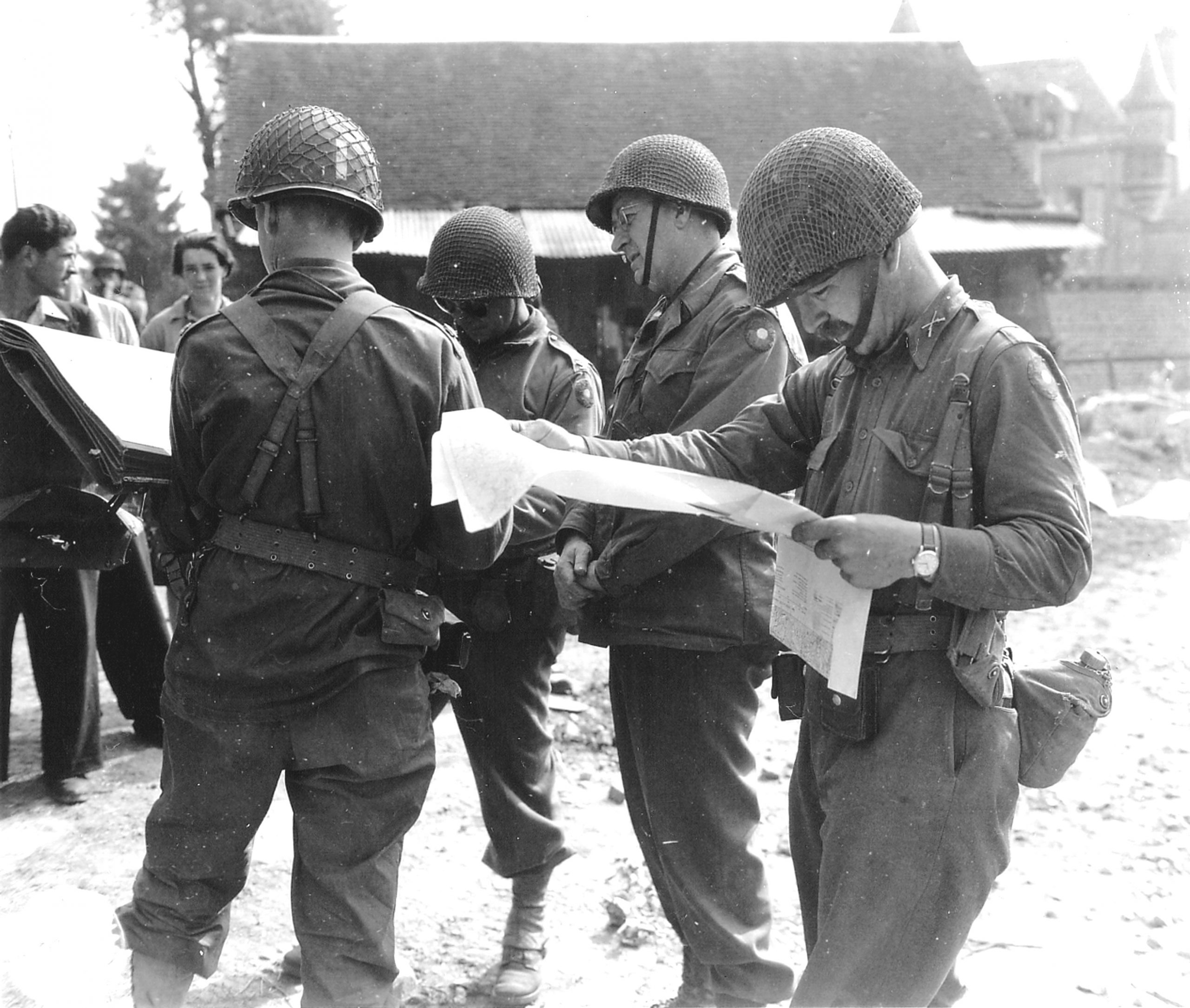 The commander of the 9th US Infantry Division, Gen Manton S. Eddy, studies a map of shortly after his division took the town of Beauvain from the Germans on August 16