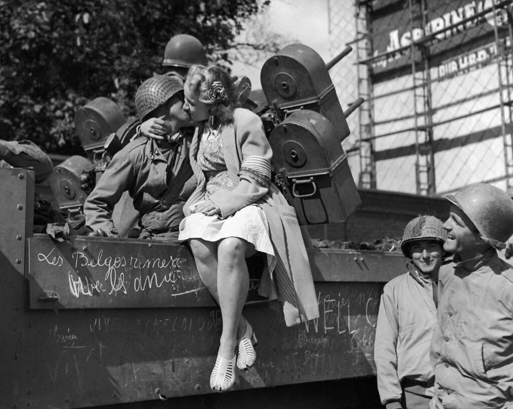 A Belgian girl kisses an American anti-aircraft gunner after the liberation of Liege, Belgium 1944