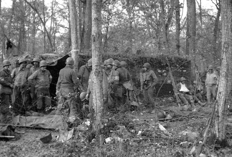 Battalion Aid Station personnel readying casualties for evacuation farther to the rear