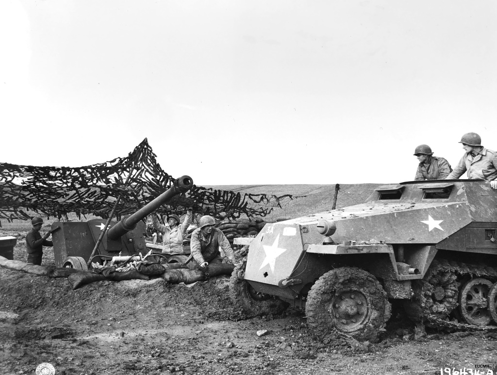 SC-196434-NARA-EUCMH Release. While ammunition is brought up in a German half-track, US Army soldiers prepare to fire a captured German 88-MM gun back into the enemy lines. October 25, 1944, France