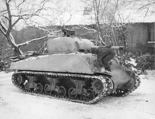 Sgt Dee Perry of the 10th Armored Division applying winter paint to his M4 Sherman tank in Belgium, 12 Jan 1945