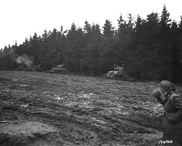 Sherman tanks mounted with 105-MM howitzers open fire in a muddy field amid the Hürtgen Forest on Nov 17, 1944