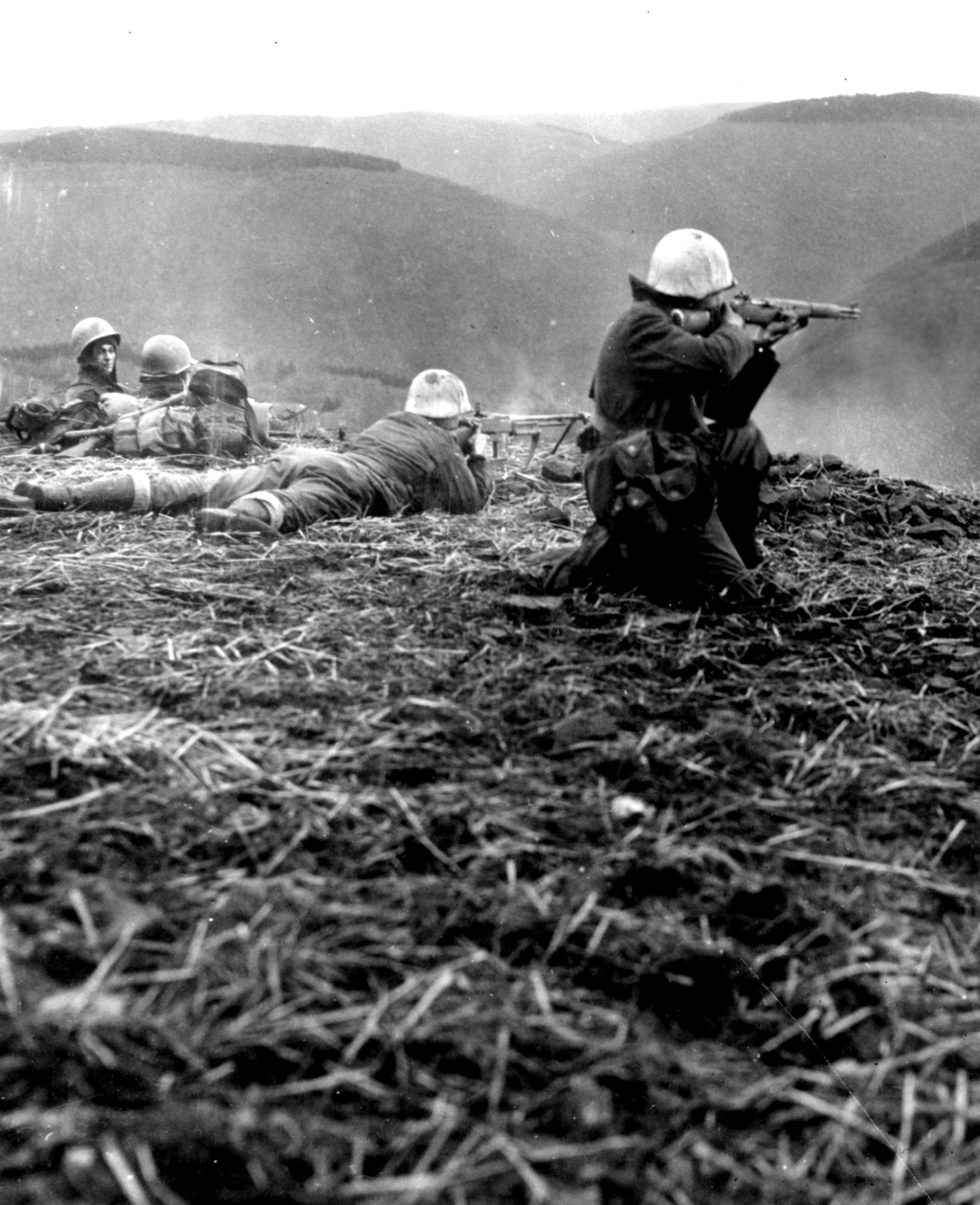 US soldiers from the 9th Infantry Division crouching and lying in prone position while shooting at enemy forces on a hilltop. Morsbach-Germany