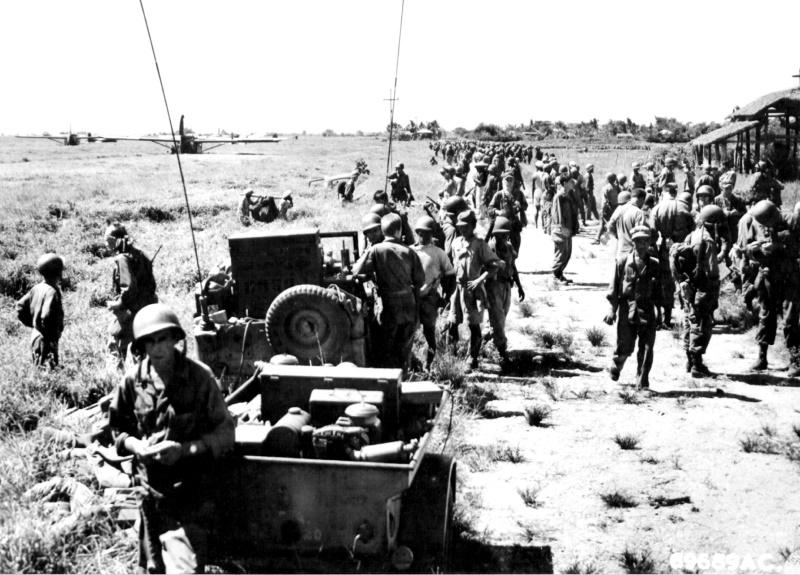 11th Airborne Division men assemble at a pre-destined point in the Philippines. This was just after their parachute landing at Appari Airstrip in Northern Luzon Island, Philippines. The landed gliders on the upper left carried field pieces, jeeps, and a trailer equipped with a long-range radio station