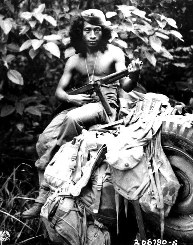 Amicedo Farola, of Dulag, Leyte, is a Philippine guerrilla scout, operating with a recon squadron of the 24th Division. The hair dress may be unusual, but Farola has more Japanese kills to his credit than he will admit to strangers. His associates confirm his scouting and fighting ability. Digos, Mindanao, March 26, 1945