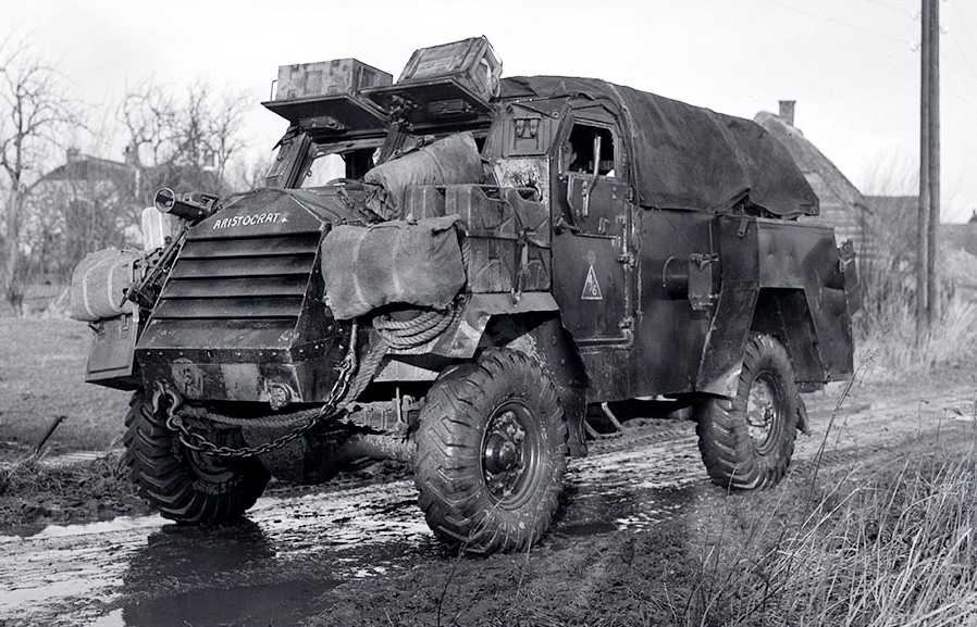 Chevrolet C15TA Armoured truck (4x4, 101-inch wheelbase, 15 cwt), CZ428917 Aristocrat near Nijmegen, Netherlands, 5 Dec 1944. Note the PIAT mounted on the starboard side (just above the ARISTOCRAT lettering), and jerry cans on the port side