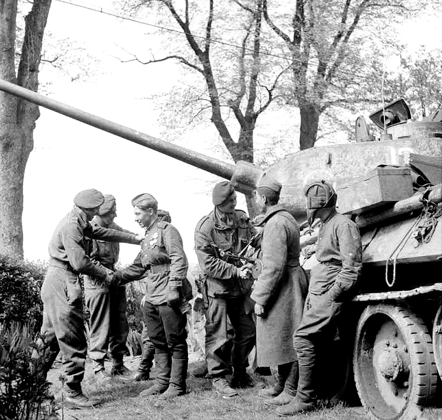 Men of the British 6th Airborne Division greet the crew of a Russian T-34 tank near Wismar, 1945