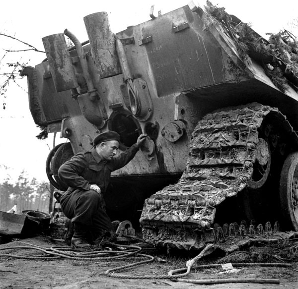 Private W.G. Lourie examining a German Jagdpanther 8.8cm. self-propelled gun which was put out of action by the first shot from a 17-pounder gun of the 6th Anti-Tank Regiment, Royal Canadian Artillery (R.C.A.), in the Reichswald, Germany, 16 March 1945