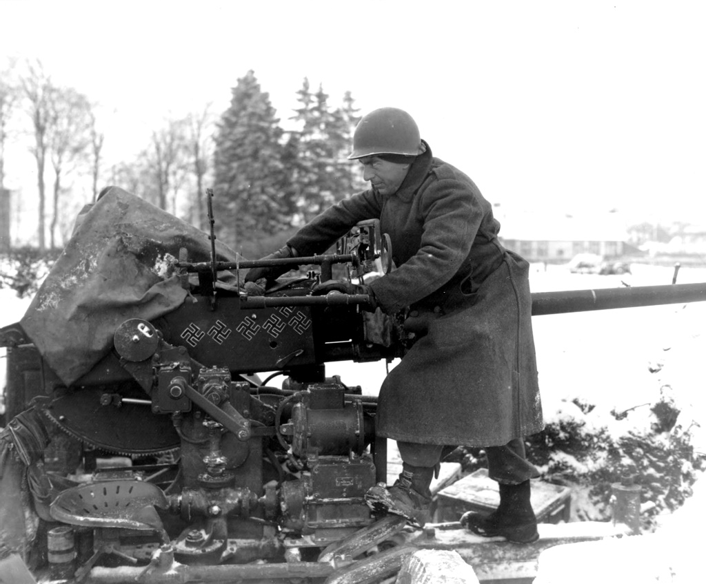 Dec 1944, Pvt Paul Romanick, taking care of his 40-MM AAA AW, B Btry, 103th AAA BN Sourbrodt (town)